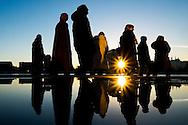 Nederland, Amsterdam, 17 jan 2016<br /> Groep mensen lopen langs een plas water waar zij in worden gereflecteerd. Ondergaande zon geeft op een heldere winterse dag een hard contrast. <br />  <br /> Foto: (c) Michiel Wijnbergh