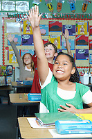 Three pupils with raised hands