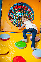 Young girl climbing up ramp into tunnel at soft play centre