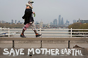 A Climate Change activist with Extinction Rebellion walks over Waterloo Bridge while campaigning for a better future for planet Earth after blocking the Thames crossing and as part of a multi-location 5-day Easter protest around the capital, on 16th April 2019, in London, England.