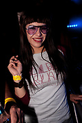 COOL ATTRACTIVE FEMALE CLUBBER IN PURPLE TINTED GLASSES RED LIPS A LONG BLACK HAIR SMILING.