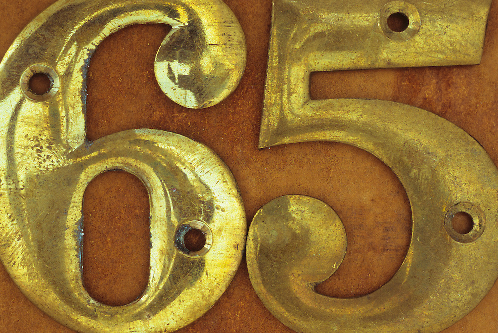 Slightly tarnished brass screw-on house numbers 65 lying on brown metal surface