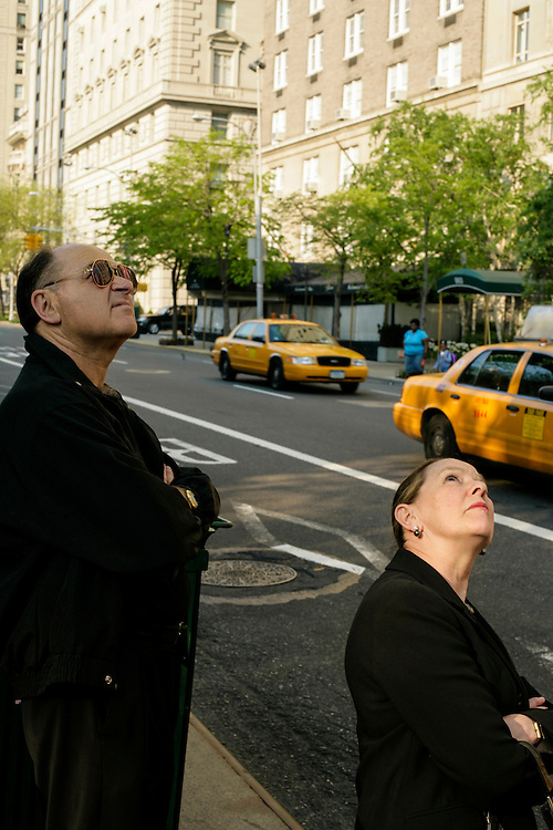 Two passers look above on a New York street.