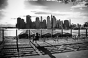 A girl is sitting on a bench on Brooklyn Heights Promenade, facing the Wall Street skyline, Brooklyn, New york