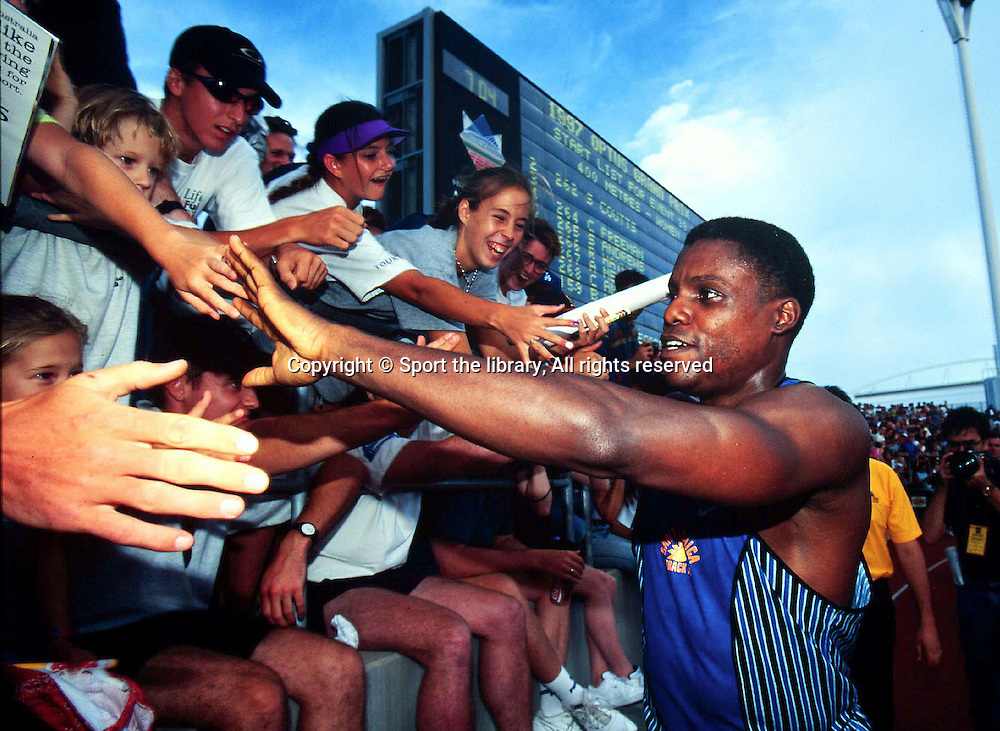 Carl Lewis (USA) exchanges hi-fives with the crowd. Athletics - Track & Field, 1997 Optus Sydney Grand Prix, Sydney Olympic Park. Photo: Sport the library/PHOTOSPORT
