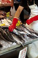A man arranges fresh fish for sale at the wet market, Hong Kong, China.