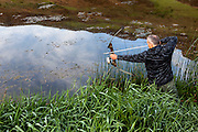 WA11808-00...WASHINGTON - Bow hunter Phil Russell hunting for bull frogs in a small pond.  (MR# R8)
