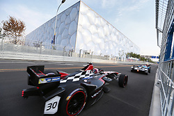 epa04398391 French driver Stephane Sarrazin (L) of Venturi Formula E team in action with the Water Cube or National Aquatic Centre in the background during the FIA Formula E Championship racing series at the Olympic Park in Beijing, China, 13 September 2014. The first Formula E race takes place in Beijing 13 September using cars powered only by electricity.  EPA/HOW HWEE YOUNG