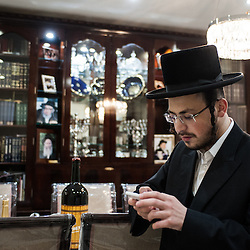 London, UK - 13 April 2014: a member of  the Jewish Community of Stamford Hill uses his mobile phone in his house on the night before Passover.