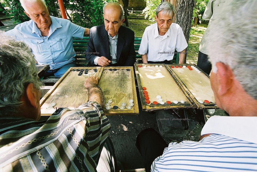 In einem Park der armenische Hauptstadt Eriwan vertreiben sich alte Männer die Zeit mit Backgammon. Some retired men playing backgammon in a park area in Yerevan, armenia.
