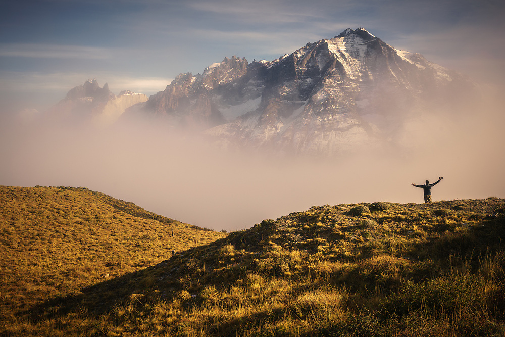 A hiker celebrates with outstretched arms as Paine Grande emerges from the fog, Torres del Paine National Park, Chile