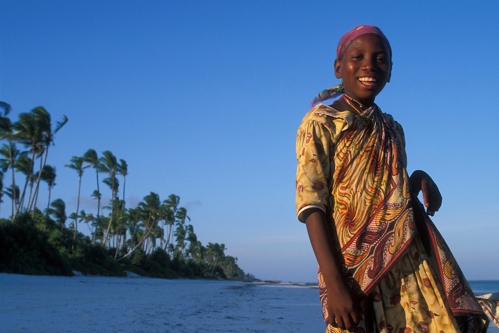 Africa, Tanzania, Zanzibar, Matemwe Bay, Portrait of young girl smiling at sunset on beach along Indian Ocean