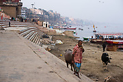 A local man walks over the riverfront steps or Ghats leading to the banks of the River Ganges, Varanasi.