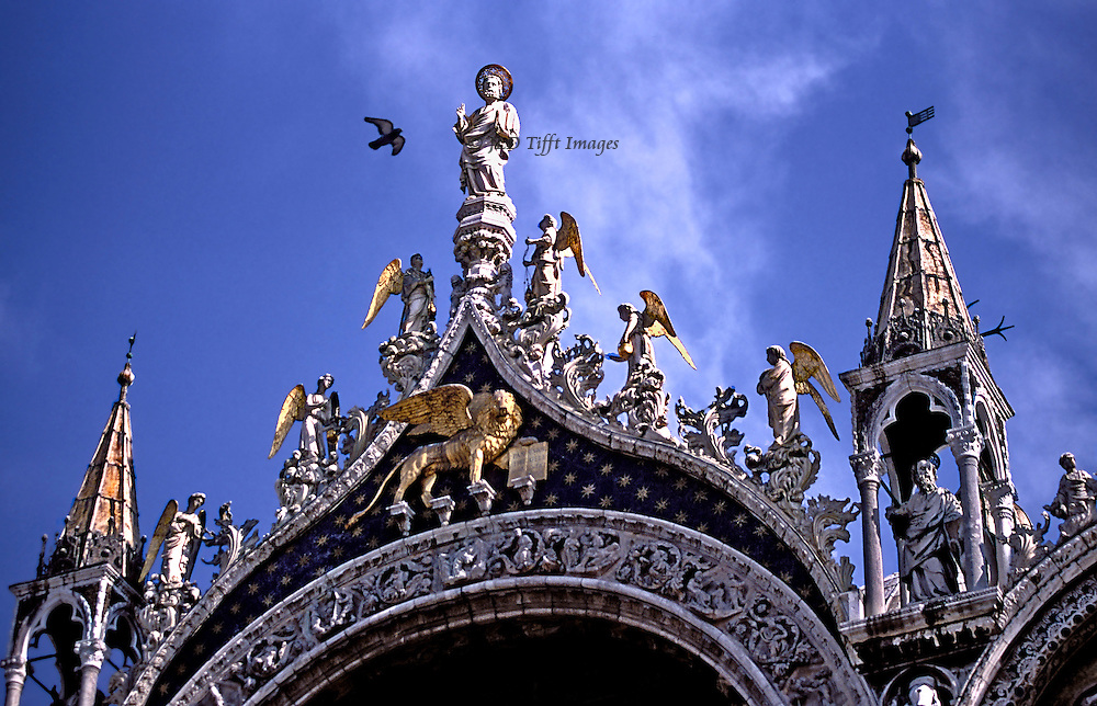 Statue of St. Mark with winged angels at peak of central doorway, San Marco, Venice, reach for the sky as they look down toward the people.  A seagull flying by seems to greet the figure of the saint and echoes the gilded wings of the angels and the winged lion of Saint Mark.