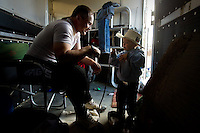 Donnie Griggs talks with his son Radley, 2, while he puts on his protective gear for bull fighting Friday at the North Idaho Rodeo.