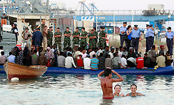 Maltese people swim in the sea as would-be immigrants wait to disembark from a dinghy in Birzebbugia in the south of Malta July 27, 2008. Ninety-five would-be immigrants were intercepted by the Armed Forces of Malta two miles off the island and escorted to shore while on their way to reach European soil from Africa, authorities said. .
