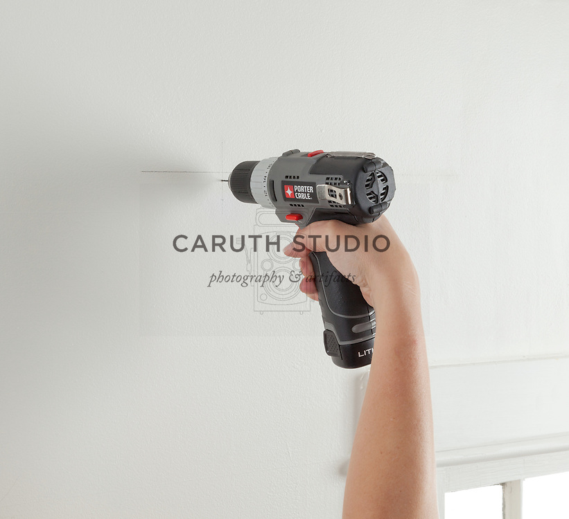 How to hang curtains: drilling pilot holes for curtain rod bracket