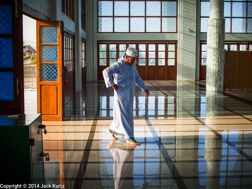 28 JULY 2014 - KHLONG HAE, SONGKHLA, THAILAND: A man walks into Songkhla Central Mosque before Eid services. Eid al-Fitr is also called Feast of Breaking the Fast, the Sugar Feast, Bayram (Bajram), the Sweet Festival and the Lesser Eid, is an important Muslim holiday that marks the end of Ramadan, the Islamic holy month of fasting.   PHOTO BY JACK KURTZ