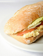 Egg sandwich in a Ciabatta roll with tomato and lettuce on a white plate