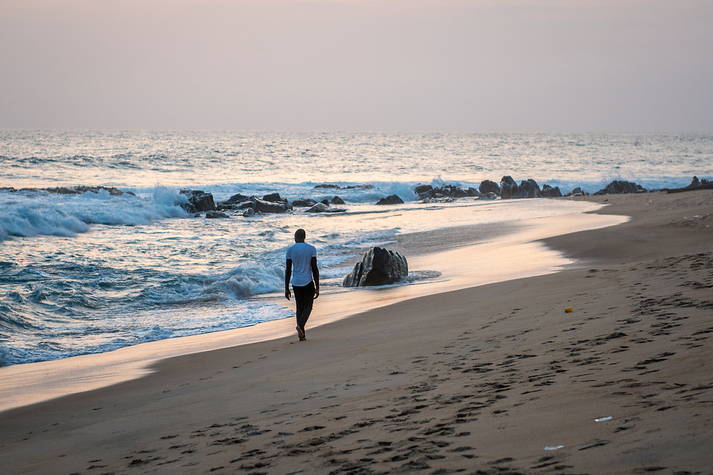 A man walks alongside the water at dusk on a beach in Monrovia, Liberia