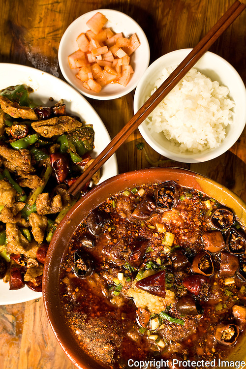 Yang Yang: 'water-boiled' beef with Sichuan peppercorn and dried chilies front, ganbian fei chang - dry-fried pig intestines with green peppers and Sichuan dried chilies - behind