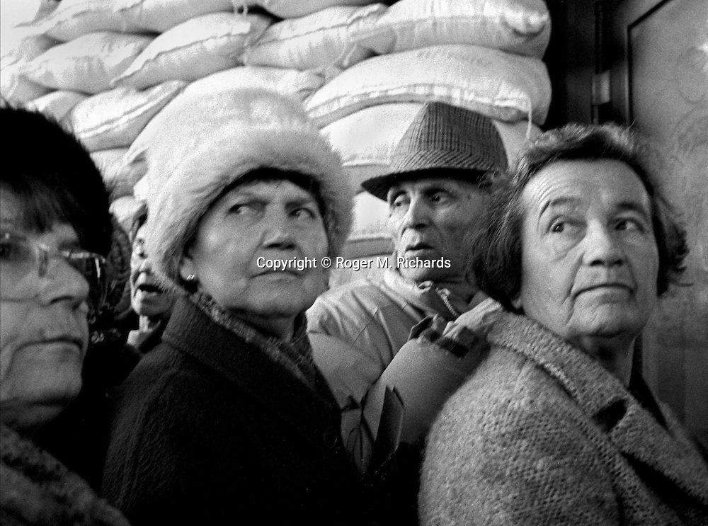 Elderly Serbs line up outside a Bosnian Serb militia post and wait anxiously for permission to cross the Bratstvo i Jedinstvo Most (Brotherhood and Unity bridge) and enter Bosnian Government-controlled Sarajevo during the final days of the siege of the city, Sarajevo, Bosnia and Herzegovina, February 1996. PHOTO BY ROGER RICHARDS