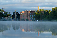 Middletown, New York - Mist moves across the lake at Fancher-Davidge Park on a cool spring morning as the sun hits the Brewery Apartments  in the background on June 5, 2012.