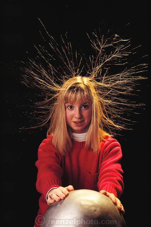 Van de Graaff generator display at the Franklin Institute in Philadelphia, Pennsylvania. Pamela Gross demonstrates static electricity. A Van de Graaff generator is an electrostatic generator used to produce a high voltage, usually in the megavolt range. Physicist Robert J. Van de Graaff invented it. The generator creates a negative charge of static electricity. When the boy touches the dome the charge passes from the dome (where it would otherwise be stored) on to his hands, and through to his hair. As the individual hairs become charged they repel each other, causing them to stand on end. (1991)
