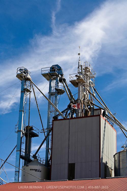 Grain storage silos or elevators under a bright blue sky.