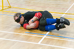Team Player catching ball during a Goalball game; a threeaside game developed for the visually impaired and played on a volleyball court, A specially adapted ball containing an internal bell is used,