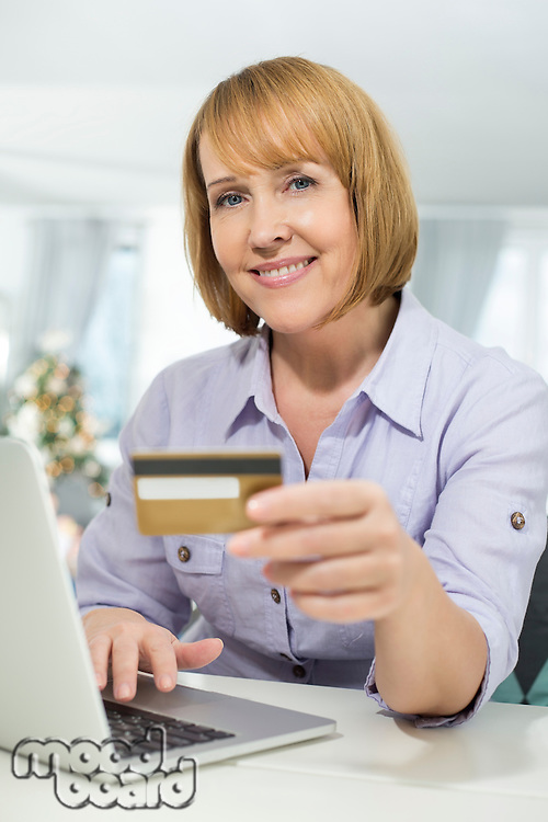 Portrait of happy woman shopping online at home during Christmas