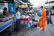 Sept. 23, 2009 -- BANGKOK, THAILAND: Women pray after making a donation to monk soliciting alms in the Khlong Toey slum section of Bangkok. Khlong Toey slum in Bangkok, Thailand, is the largest slum area in Bangkok. Photo by Jack Kurtz