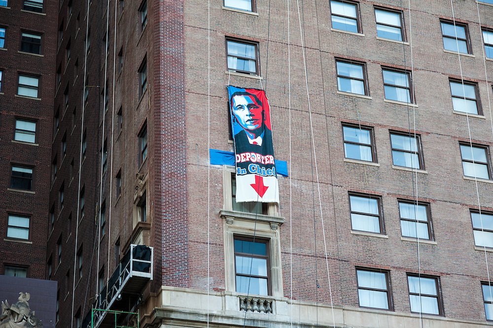 "A banner reading ""Deporter In Chief"" is hung from a window at the Hilton Chicago hotel."