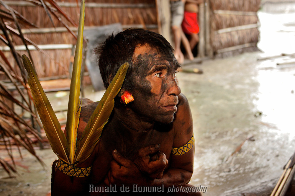Viriunaveteri, Venezuela.  A Yanomami man watching a tribal dance. ..The village of Viriunaveteri consists of 15 huts around a muddy square. It's situated in the Venezuelan Amazone several days by boat from the nearest town. This community on the banks of the Casiquiare is one of the few Yanomami villages that actually has some contact with the outside world. Most other tribes live deeper in the jungle.