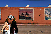 Local women out shopping on market day in Tazenakht walk by a mural depicting scenes of the nearby Sahara desert.
