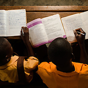 Asig (left) and Huudi, pictured at a government school in the Upper West Region of Ghana on 27 May 2014, share an English textbook because there are not enough to go round. When they have homework, they work in a group with their classmates.