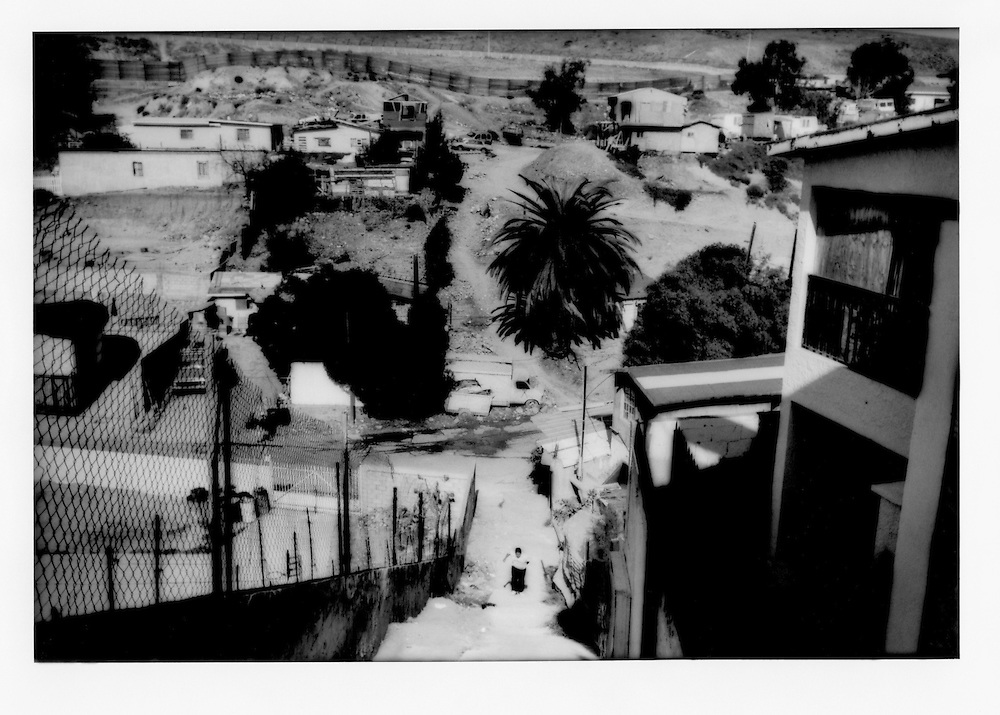 Young man ascends long stairway within sight of the Mexican border fence and American border wall, in dusty Colonia Libertad, Tijuana, Mexico.   Tijuana does not possess as much water as San Diego, California and more reflects the natural climate of the region.