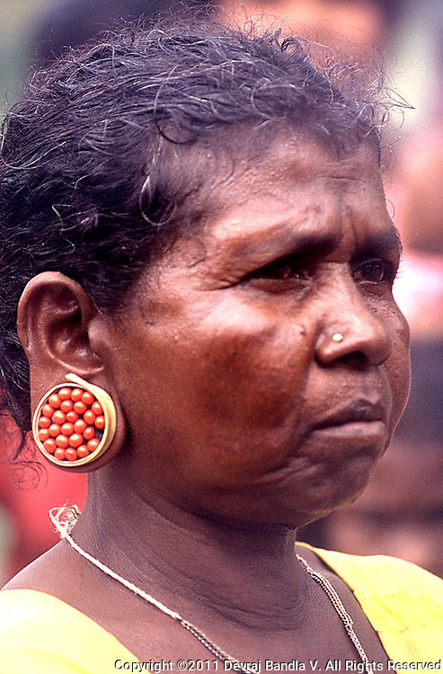 Woman belonging to the Pania tribe wearing an ear ornament made with palm leaf.and red 'Gundu mani' seeds,Wayanad,Kerala,India.