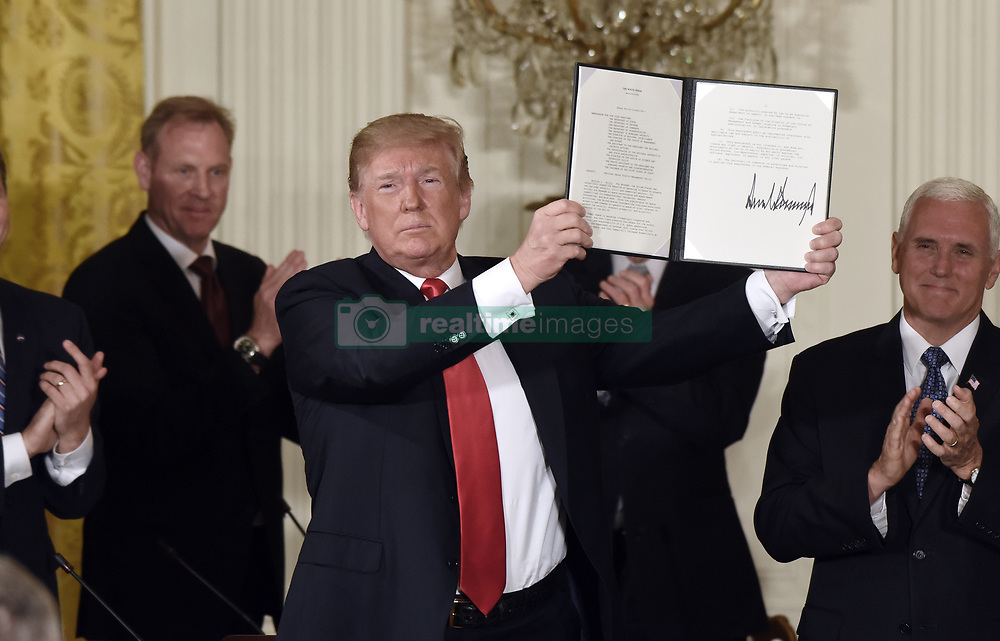 President Donald Trump holds a signed National Space Directive to establish Space Traffic Management program to address challenge of congestion of satellites and space vehicles in Earth orbit during a meeting with the National Space Council in the East Room of the White House, in Washington, D.C., on June 18, 2018. Photo by Olivier Douliery/ Abaca Press