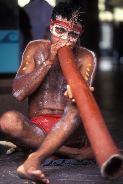Australia, New South Wales, (MR) David Kennedy, wearing traditional Aboriginal face and body paints, plays the dijeradoo in Sydney