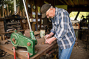 Bob Denman of Red Pig Tools measures a metal rod to make a new tool.
