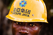 "A Guinean worker wears a helmet from Chinese construction company ""Groupe Jinya"" on the construction site of the Kipe hospital in Conakry, Guinea on Wednesday March 4, 2009. The Kipe hospital is a 10 million dollars project entirely funded by the Chinese government. (Olivier Asselin for the New York Times)"