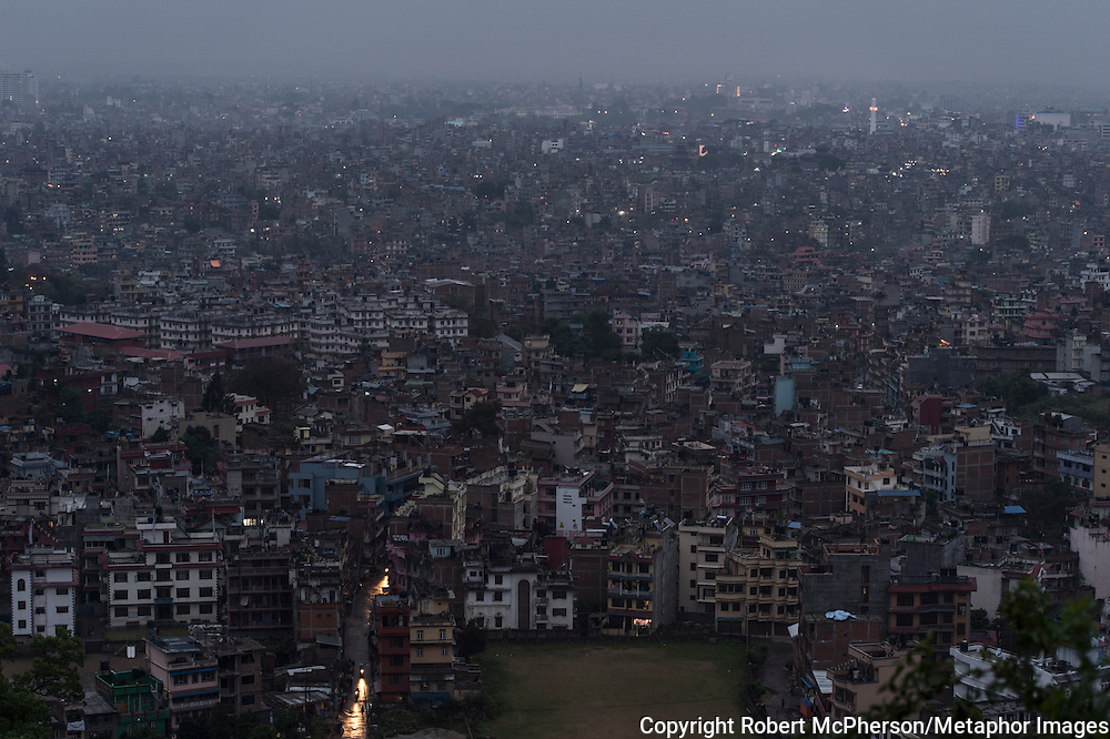 An overview over Kathmandu before sunset shows small, fragmented rays of light in the windows. Restricted use of electricity in the city is evident. At summer time the electricity is turned off for 8 hours a day. Nepal is the second richest country in water resource but they still meet challenges with building hydropower. Everyday electric current goes off for hours and people are compelled to live in the darkness. Norway is one of the countries who have earned a lot of money on building hydropower in Nepal, but the country itself still remains poor and undeveloped. After the earthquakes that struck Nepal in 2015 the situation is even worse.
