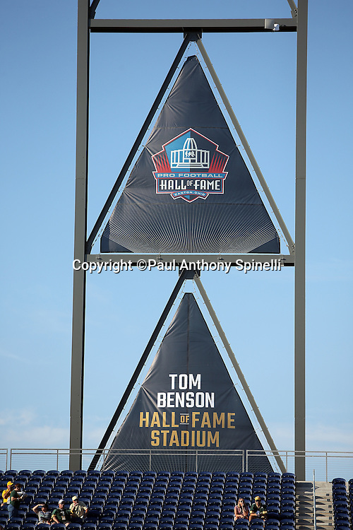 The Pro Football Hall of Fame logo appears on a large banner above the field at Tom Benson Hall of Fame Stadium before the Green Bay Packers 2016 NFL Pro Football Hall of Fame preseason football game against the Indianapolis Colts on Sunday, Aug. 7, 2016 in Canton, Ohio. The game was canceled for player safety reasons due to the condition of the paint on the turf field. (©Paul Anthony Spinelli)