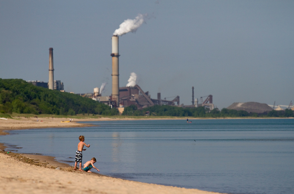 Children play in the water at Indiana Dunes State Park in Chesterton, Indiana as a factory looms in the distance.