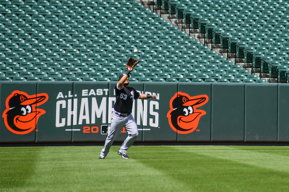 Baltimore, MD - April 29, 2015: White Sox left fielder Melky Cabrera catches a fly ball to the backdrop of empty seats at Oriole Park at Camden Yards on April 29, 2015. The civil unrest in Baltimore has forced the game between the Chicago White Sox and Baltimore Orioles to be closed to the public and moved to the afternoon. (Matt Roth for ESPN)