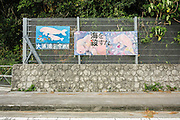 'Save the dugong' bill boards on a coastal road.  Camp Schwab,  a U.S. military base in Henoko is under expansion. Construction will double its current size and will eventually include two airstrips. In order to do this plans to reclaim land in the surrounding sea are afoot. This will permanently damage the coral reefs and the feeding grounds of the dugong, an endangered species. Henoko, Okinawa, Japan.