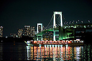 """The lights of a """"yakata-bune"""" pleasure boat are reflected in the calm waters of Tokyo Bay, Japan on 31 August  2010. .Photographer: Robert Gilhooly"""