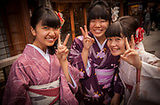 Young women dressed in traditional kimonos give peace symbol, Kyoto, Japan