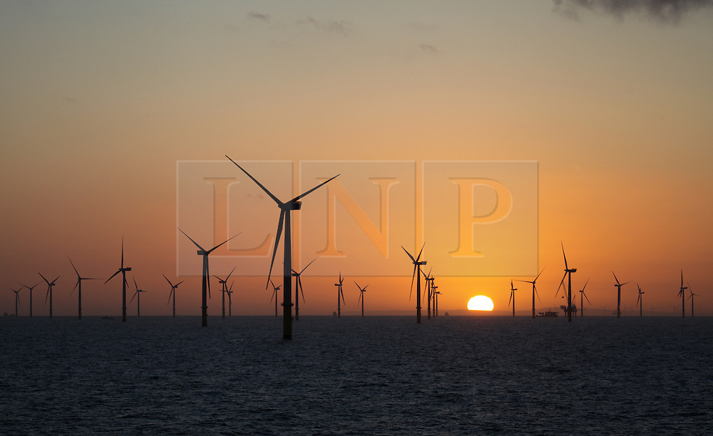 © Licensed to London News Pictures. 18/04/2014. North Wales, UK. The sun rising over the partially constructed Gwynt y Môr Offshore Wind Farm off the coast of North Wales this morning, Good Friday, 18th April 2014. Photo credit : Rob Arnold/LNP